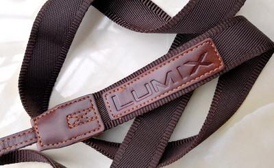 一个松下LX系列相机用的栗棕色帆布背带(上面一侧有英文LUMIX字